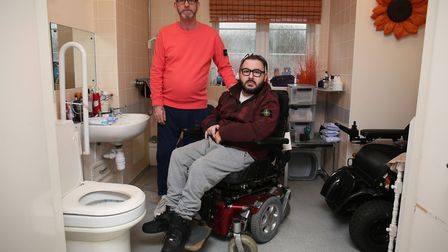 Carer Nigel Gordon with stepson Danny King-Gordon in the bathroom which floods Danny's bedroom and h