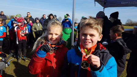 Imogen Holland and Samuel Stacey show off their Muddy Monsters medals.