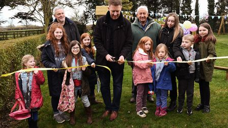 Russell Payne, centre, delares the play park open with youngsters from the village and, left, fundra