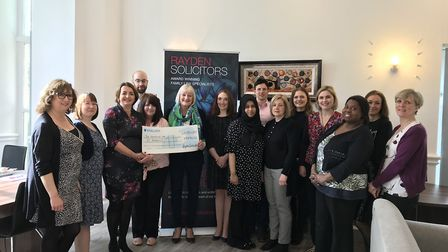Carolyn Addison (in front of the banner) receiving the cheque from the Rayden Solicitors team, inclu