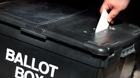 Someone putting their vote into a ballot box.