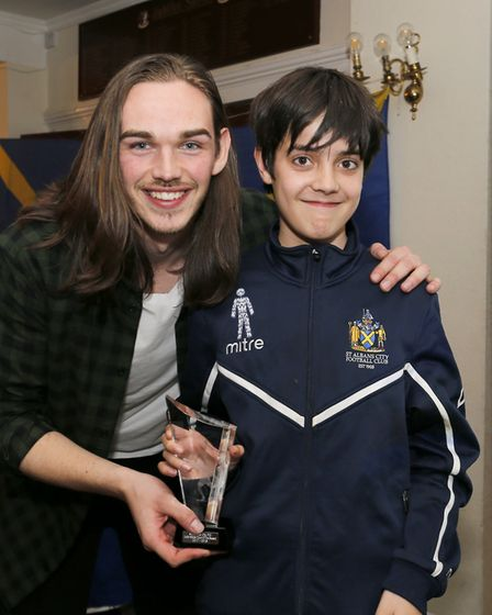 Zac Hill on behalf of the Young Saints club presents Tom Bender with the Young Saints player of the