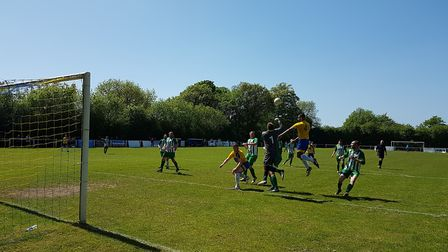 Harpenden Town's Dwayne Duncan challenges for a header with Holmer Green goalkeeper Aaron Brown.