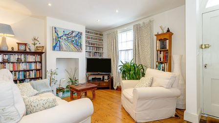 The sitting room has exposed timber floorboards