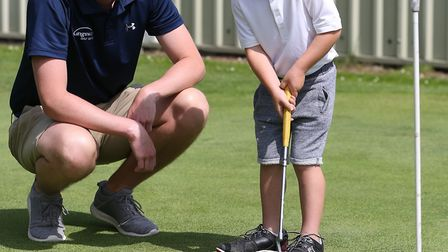 Marcus Karim, four, gets some putting tips from Kingsley Golf centre PGA professional Chris Hattersl