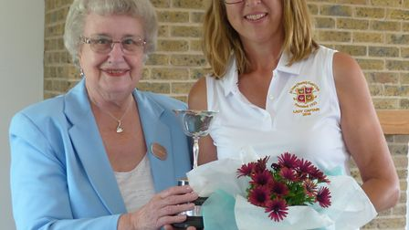 Claire Pendall receives the trophy from county president Maureen Mansfield.