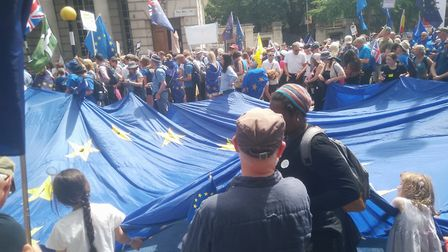 Protestors holding a huge flag of the European Union, expressing their support.