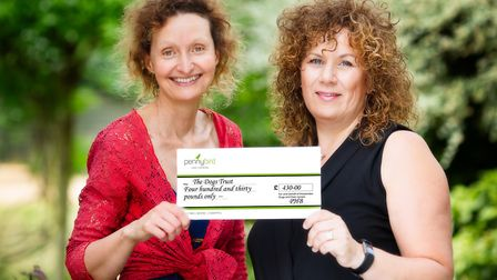 Photographer Penny Bird hands over a cheque for 430 to manager of Harpenden Dogs Trust Charity Shop