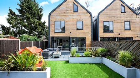 The rear garden has a large seating area complimented by an artifical lawn and raised planters