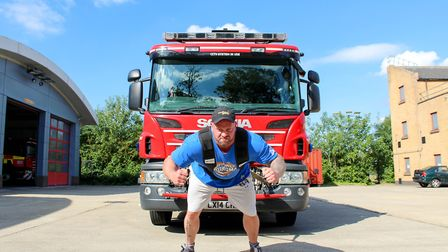UK's Strongest Man competitor Phil Roberts attempting to pull a fire engine at St Albans fire statio