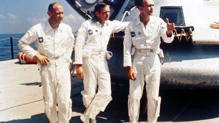 UNeil Armstrong, Michael Collins and Edwin Buzz Aldrin standing by a boiler plate Apollo capsule o