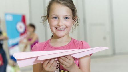 A youngster at IWM Duxford has a go at making an aerodynamic paper plane. Picture: IWM.