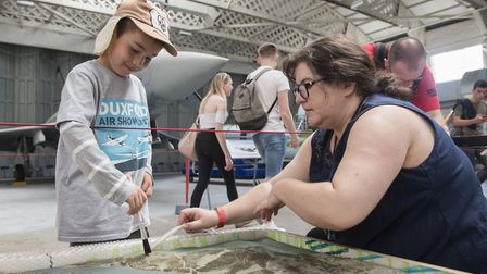 A young visitor helps an IWM Duxford conservator to keep a museum object in tip-top condition. Pictu