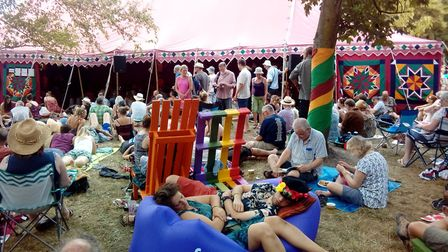 The crowd outside The Den at Cambridge Folk Festival, the couple in front at fast asleep