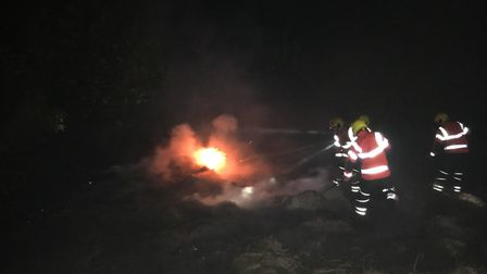 Firefighters tackle a blaze in a stack of grasss at Cambourne