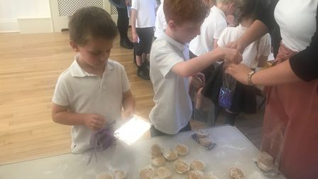 Year 1 pupils putting their cakes in the bags. Picture: Therfield First School