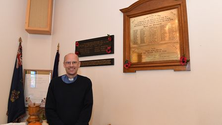 Reverend Andrew Prout stands in front of the relocated First and Second World War memorials. Picture