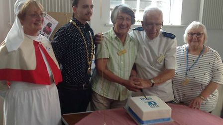 Peter, pictured wearing his old uniform, cutting a cake for the 70th anniversay of the NHS with othe