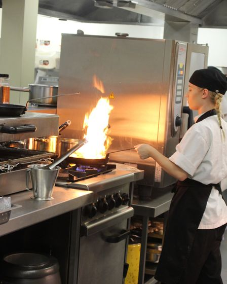 A student working in the kitchen at The Stables restaurant.