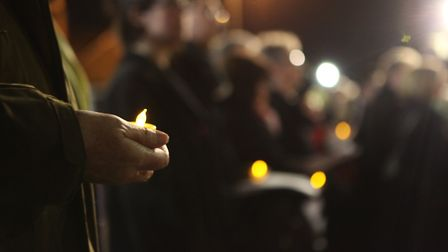 A man holds one of the 650 LED Candles which represent every soldier on the war memorial during the