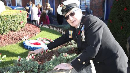 Petty Officer, Reginald Bragg places a cross on the war memorial for his family member Harry Bragg w