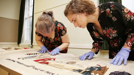 The Royston tapestry is unveiled and checked by Royston Museum assistant Amy Judd and curator and ma