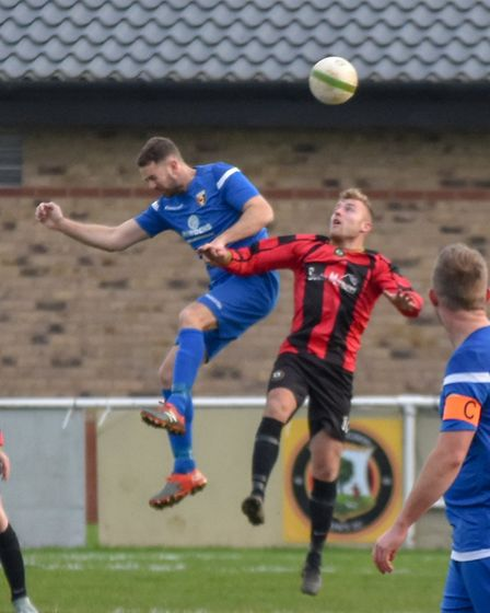 Adam Richardson challenges in the air during Huntingdon Town's home defeat to Rushden & Higham. Pict