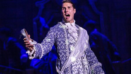Prince Charming holding Cinders' glass slipper in pantomime Cinderella at The Alban Arena in St Alba