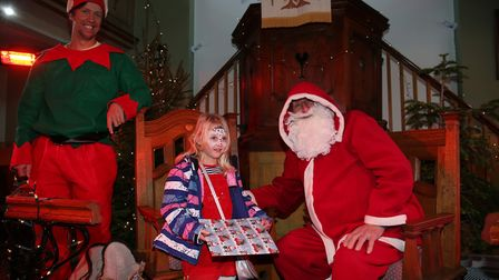 Lottie Wilson, five, receives a gift from Santa in the winter wonderland at Ashwell at Christmas. Pi