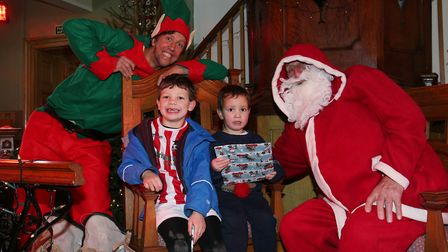 Jack, six, and James Edwards-Cliffe, three, receive their gifts from Santa in the winter wonderland