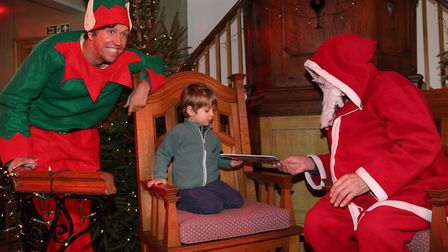 Rider Pertwee, two, receives a gift from Santa in the winter wonderland at Ashwell at Christmas. Pic