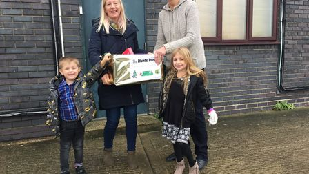 Debbie Davies, from The Hunts Post, with Ben and Lucy Davies handing over food donated by Hunts Post