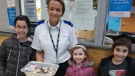 At Hatfield Police Station, an officer accepts a delivery of 'thank-you' cupcakes on Christmas Day f