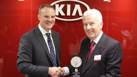 Managing director John Mantle is presented with a platinum dealer award by Simon Hetherington, comme
