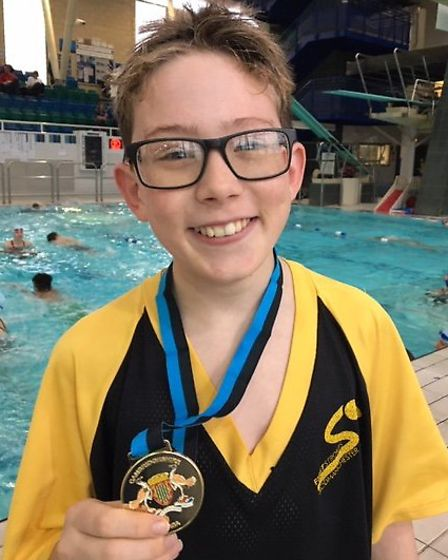 Riley Hall shows off his historic gold medal for First Strokes Godmanchester.