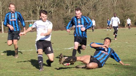 A Harpenden Colts Old Boys defender blocks a shot from four-goal James Todd of Welwyn Warriors.
