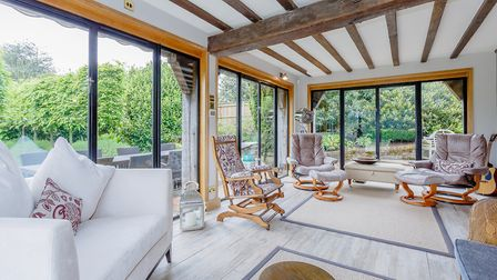 The garden room is a modern addition, with glass walls overlooking the landscaped grounds to the rea