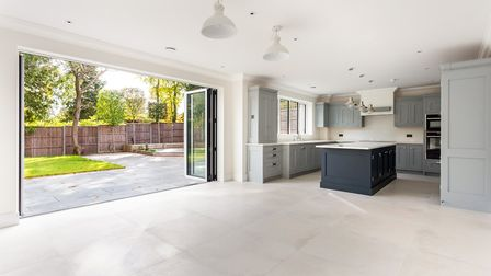 The kitchen is open to a spacious and versatile family room/dining space with bi-fold doors onto the