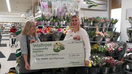 Christine Phillpotts, a Pinpoint trustee, receives a cheque from a Waitrose employee