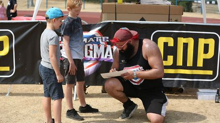 Finley, 10 and Loui Hayes, seven, with strongman Ashton Reid at a kids strongman course at the UK's