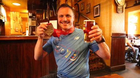 John Adamson with his medal and a well-deserved pint. Picture: Khandel Light