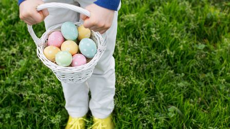 close-up view of eggs in easter basket being held by little boy after easter egg hunt