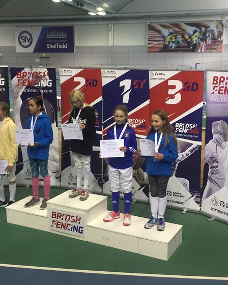 Paul Davis Fencing Academy's Maya Sutton on the podium after winning bronze in the U12 sabre at the