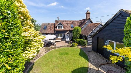 The sun-trap rear garden has a sunken paved patio, shaped lawn and ornamental pond. Picture: Charter