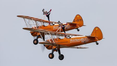 The AeroSuperBatics wingwalkers performing at the 2019 Duxford Air Festival over the Spring May Bank