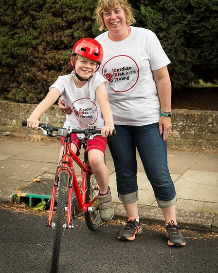 Ollie Higman-Hall with his mum Kirsty Higman. The eight-year-old is cycling 10 miles for CRY, after