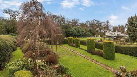 The private front garden has wide areas of lawns with attractive planting and a path to the front do