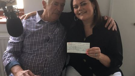 Ted hands over a cheque to Zoe at Black Cat radio. Picture: CONTIRBUTED