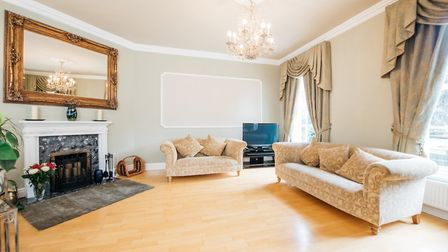 The sitting room has two sash windows to the front and a feature open fireplace with a marble surrou