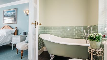 The en suite has a free standing roll top bath as well as an enclosed shower cubicle. Picture: Micha